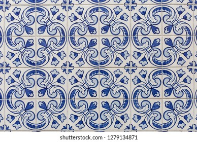 a pattern of traditional white Portuguese tiles painted with blue tracery