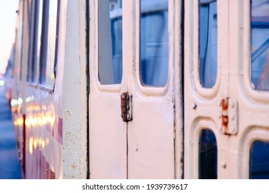 a pattern of tramcars, the front door with windows and details of an old iron tram standing together with other vehicles on the background in the evening traffic jam on the city road, close-up