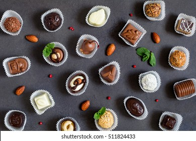 Pattern of various chocolates, almonds, mint leaves and red peppercorns. Sweet food flat lay on dark grey background, top view. Fine chocolates