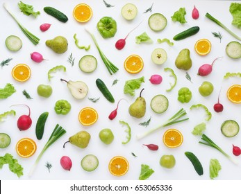 Pattern of vegetables and fruits. Abstract food background. Top view. Composition of pears, green peppers, cucumbers, green radish, green apples, pink radishes and oranges  on a white background.