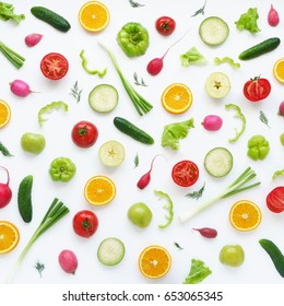 Pattern of vegetables and fruits. Food background.Top view. Composition of pears, green peppers, cucumbers, green radish, tomatoes, green apples, pink radishes and oranges  on a white background.