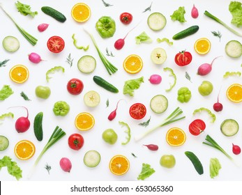 Pattern of vegetables and fruits. Food background.Top view.Composition of pears, green peppers, cucumbers, green radish, tomatoes, green apples, pink radishes and oranges  on a white background.