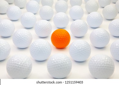 Pattern with white and orange golf balls on the table.