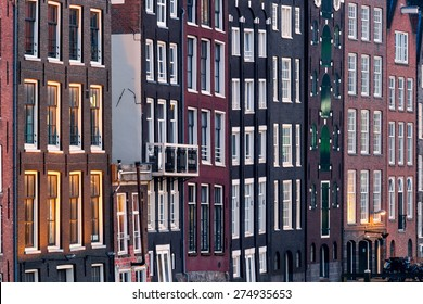 Pattern of windows, compressed tightly by telelens, of traditional quaint houses in Amsterdam, capital of Holland, Netherlands, showing irregularities in the construction of these vintage buildings