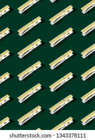 Pattern of yellow polka-dots clothespins on dark green background.