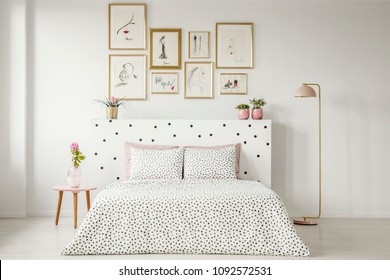 Patterned bedding on bed with bedhead in woman's bedroom interior with pink flower on table