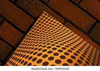 Patterned black dots round boards in a huge stone wall.