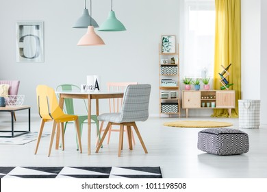 Patterned, black and white pouf in pastel dining room interior with colorful chairs standing at a wooden table