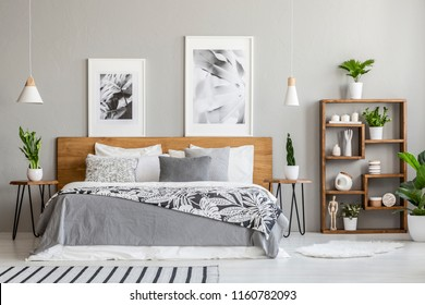 Patterned blanket on wooden bed between tables with plants in bedroom interior with posters. Real photo