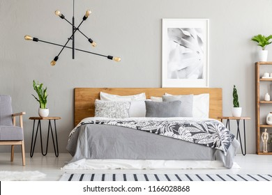 Patterned blanket on wooden bed and armchair in grey bedroom interior with poster and plants. Real photo