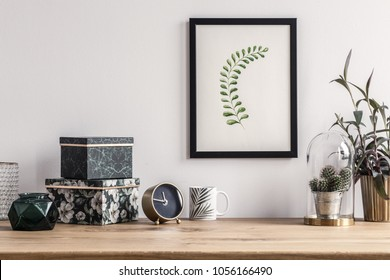 Patterned boxes and cactus standing on a wooden table in a room with poster on the wall