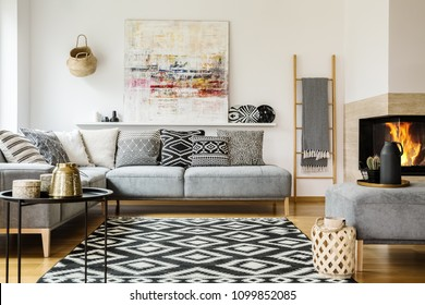 Patterned carpet in decorative living room interior with painting above couch. Real photo