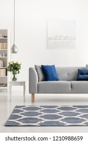 Patterned carpet in front of grey couch with blue pillows in white loft interior with flowers. Real photo