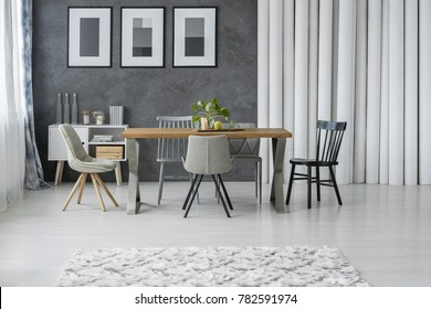 Patterned carpet in grey dining room with wooden table and chairs next to cupboard and paper tubes