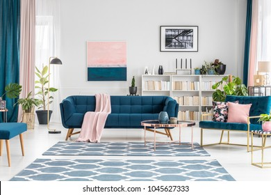 Patterned carpet in luxurious living room interior with blue sofa against white wall with pink painting