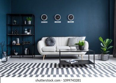 Patterned carpet in navy blue living room interior with black table in front of beige couch
