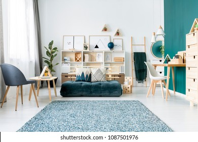 Patterned carpet near armchair and emerald mattress in colorful living room interior with chair at desk