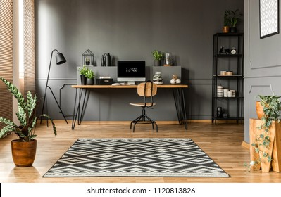Patterned carpet and plants in scandi grey home office interior with wooden chair at desk