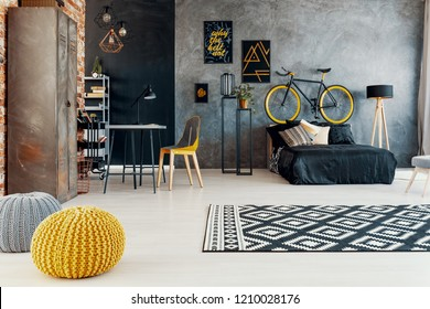 Patterned carpet and yellow pouf in grey bedroom interior with bicycle above black bed. Real photo
