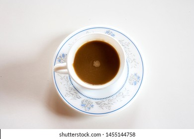Patterned coffee cup and coffee on white background
