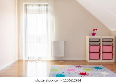 Patterned colorful carpet in kid's room interior with shelves and window. Real photo