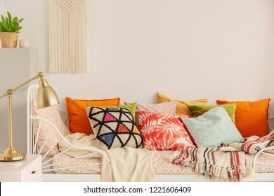 Patterned and colorful pillows on comfortable white bed in stylish bedroom interior with golden lamp on bedside table and handmade macrame on white wall, real photo with copy space