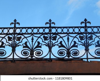 Patterned lattice of metal fence against the blue sky