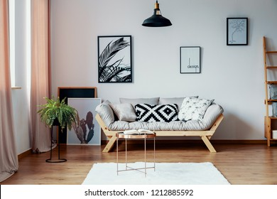 Patterned pillow on scandinavian sofa in stylish interior with gallery of poster, real photo