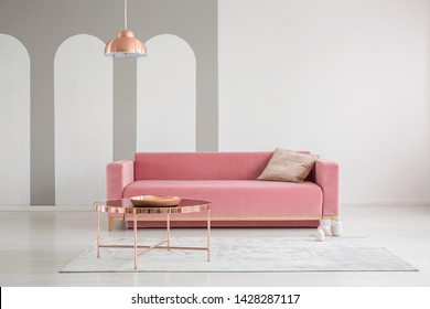 Patterned pillow on a velvet pink sofa and copper gold accessories in a feminine living room interior with empty white wall