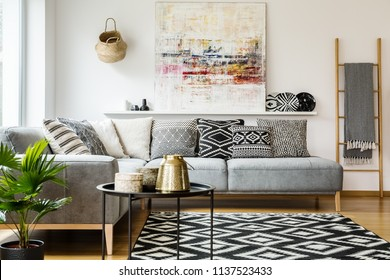 Patterned pillows on grey corner sofa in living room interior with table and painting. Real photo