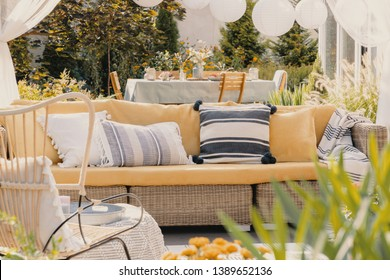 Patterned pillows on a wicker couch in a garden. Blurred close-up of a plant. Real photo