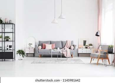 Patterned wooden armchair in white living room interior with pink pillows on grey sofa. Real photo