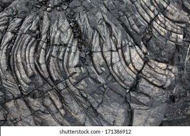 Patterns cracks and shapes emerge from this close up portion of black solidified lava on the island of Hawaii