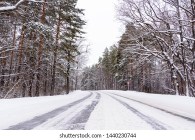 Patterns on the winter highway in the form of four straight lines. Snowy road on the background of snow-covered forest. Winter landscape.