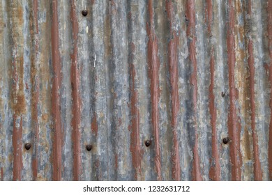 Patterns of rust, old paint and corrugation in the metal wall of an old barn for background purposes