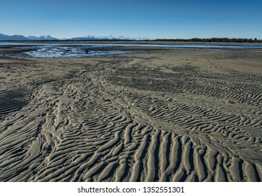 Patterns in the sand on a beach near Gustavus Alaska at low tide on a sunny day.