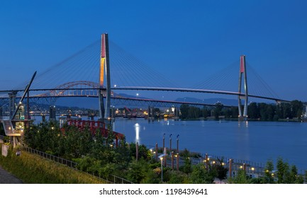 Pattullo Bridge, Sky Train Bridge  and Railroad Track over the Fraser River between New Westminster and Surrey, Promenade quay at Fraser River in New Westminster city in night time.  British Columbia