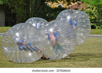 PAU, FRANCE - JUNE 06 2015: Several people fight inside of the large transparent plastic spheres outdoors in the park of PAU, FRANCE - JUNE 06 2015.