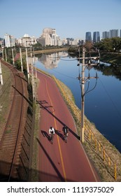 São Paulo, São Paulo / Brazil - 08/15/2015: People riding a bike on bicycle path on the banks of the Pinheiros River, west area of the city