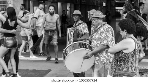 """São Paulo, Brazil - April 29th 2018 - Black and white shot of a Traditional Brazilian """"Forro"""" Band playing a couple dancing and people watching and having fun in background."""