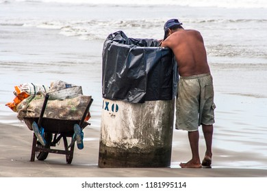 São Paulo, Brazil, December 04, 2009. Man looks for aluminum cans for recycling in a trash bin at Stela Maris beach in Peruibe, south coast of São Paulo.