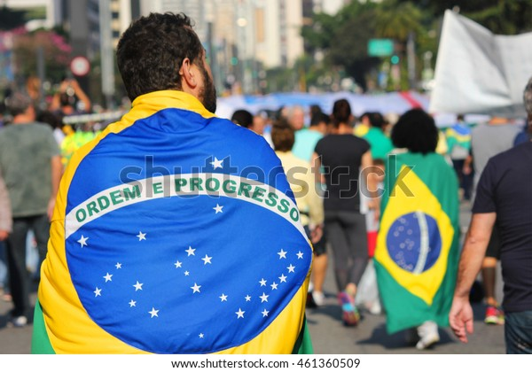 SÃ?O PAULO, BRAZIL - JUL 31, 2016: protesters march on Paulista Avenue against corruption in Brazil. Man carrying Brazilian flag on his back.