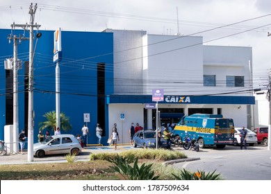 São Paulo, Brazil - July 31, 2020: agency of the federal savings bank with a queue of people with a mask to receive government assistance due to the Covid-19 pandemic. Strong car delivering money.