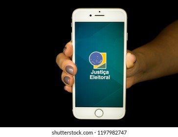 São Paulo, Brazil - October 2018: Young female hand holding mobile phone with Brazilian application for elections (translation: electoral justice). Voter's title in Brazil. Smartphone Elector e-title.