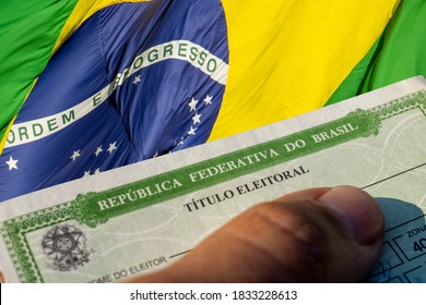 São Paulo, Brazil - September 2, 2020: detail of the title of Brazilian voter (título eleitoral) and flag of Brazil. 2020 elections in Brazil.