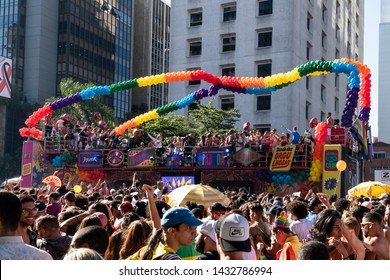 São Paulo, SP / Brazil - June 23, 2019: Crowd of young people enjoying the party with truck full of colorful balloons in the background during the LGBT Pride Parade on Avenida Paulista.