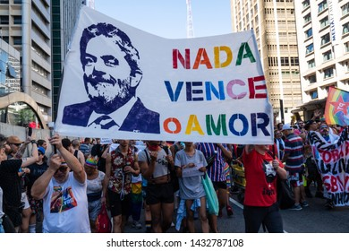 """São Paulo, SP / Brazil - June 23, 2019: People protesting for the freedom of ex president Lula with flags of """"Free Lula"""" during the LGBT Pride Parade on Avenida Paulista."""
