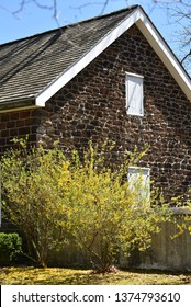 Paulsboro, NJ/USA-April 16, 2019:  Old stone church built in the 1700s.  Fine stone workmanship, blooming forsythia bush in the foreground.