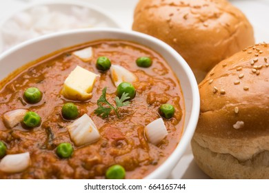 Pav Bhaji is a fast food dish from India, Thick and spicy vegetable curry, fried and served with a soft bread roll/Bun Paav and butter. Served over colourful or wooden background. selective focus