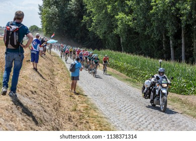 Pave Escaudoeuvres a Thun, France - July 15 , 2018: The peloton riding on a cobblestone road during the stage 9 of Le Tour de FRance 2018